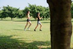 Diviértase con dos mujeres jovenes que activan en parque de la ciudad Imagen de archivo libre de regalías