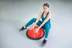 Diviértase el ejercicio de la mujer con una bola de los pilates en el gimnasio, sonriendo y mirando la cámara imagenes de archivo