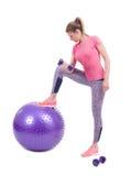 Diviértase el ejercicio de la mujer con una bola y pesas de gimnasia de los pilates Imagenes de archivo