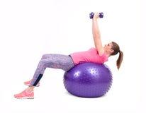 Diviértase el ejercicio de la mujer con una bola y pesas de gimnasia de los pilates Foto de archivo