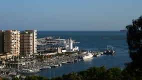 Diviértase el puerto, los muelles, el faro y los edificios con el mar azul en el puerto de Málaga, España almacen de metraje de vídeo