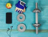 Diviértase la botella de los artículos, pesas de gimnasia, guantes en el suelo del deporte Foto de archivo libre de regalías