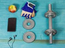 Diviértase la botella de los artículos, pesas de gimnasia, guantes en el suelo del deporte Imagen de archivo libre de regalías