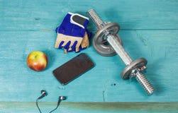 Diviértase la botella de los artículos, pesas de gimnasia, guantes en el suelo del deporte Imagenes de archivo