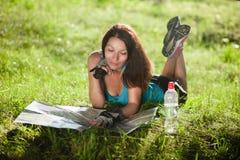 Diviértase la endecha de la muchacha del viaje en una hierba y lea un mapa Imágenes de archivo libres de regalías