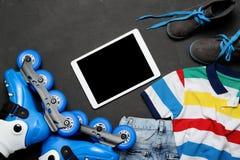 Diviértase, la forma de vida sana, los pcteres de ruedas y el sistema de la ropa del ` s del muchacho, teléfono celular en fondo  Fotos de archivo