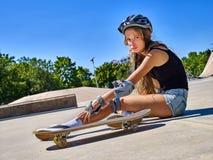 Diviértase a la muchacha con lesión cerca de su monopatín al aire libre Foto de archivo libre de regalías