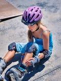 Diviértase a la muchacha con lesión cerca de su monopatín al aire libre Imagen de archivo libre de regalías