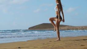 Diviértase a la muchacha en una playa que hace ejercicios de las estocadas Concepto de una forma de vida sana almacen de video