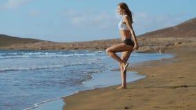 Diviértase a la muchacha en una playa que hace ejercicios de las estocadas Concepto de una forma de vida sana almacen de metraje de vídeo