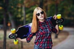 Diviértase a la muchacha feliz que presenta en verano con el monopatín Mujer afortunada elegante del inconformista con longboard  Imagenes de archivo