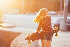 Diviértase a la muchacha feliz que presenta en verano con el monopatín Mujer afortunada elegante del inconformista con longboard  Fotos de archivo