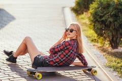 Diviértase a la muchacha feliz que presenta en verano con el monopatín Mujer afortunada elegante del inconformista con longboard  Imágenes de archivo libres de regalías