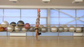 Diviértase a la muchacha que intenta llevar a cabo la balanza en las manos en gimnasio metrajes