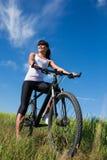 Diviértase a la mujer de la bici en el prado con un paisaje hermoso Fotografía de archivo libre de regalías