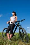 Diviértase a la mujer de la bici en el prado con un paisaje hermoso Fotos de archivo libres de regalías