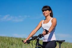 Diviértase a la mujer de la bici en el prado con un paisaje hermoso Foto de archivo libre de regalías