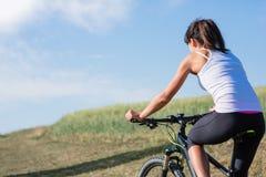 Diviértase a la mujer de la bici en el prado con un paisaje hermoso Foto de archivo