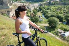 Diviértase a la mujer de la bici en el prado con un paisaje hermoso Fotografía de archivo
