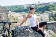 Diviértase a la mujer de la bici en el prado con un paisaje hermoso Imagen de archivo libre de regalías
