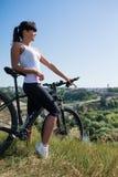 Diviértase a la mujer de la bici en el prado con un paisaje hermoso Imágenes de archivo libres de regalías