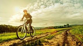 Diviértase a la mujer de la bici en un prado con un paisaje hermoso Fotografía de archivo libre de regalías