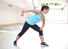 Diviértase a la mujer en azul con la pesa de gimnasia que hace ejercicio trasero de la extensión del tricep Imágenes de archivo libres de regalías