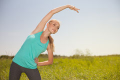 Diviértase a la mujer joven rubia de la belleza que ejercita en la yoga del aire libre Imágenes de archivo libres de regalías