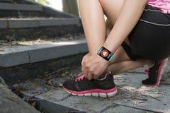 Diviértase a la mujer que ata los cordones que llevan ingenio del smartwatch del sensor de la salud Imagen de archivo libre de regalías