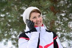Diviértase a la mujer que habla en el teléfono en bosque del invierno del pino Imagen de archivo