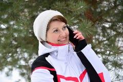 Diviértase a la mujer que habla en el teléfono en bosque del invierno del pino Fotografía de archivo libre de regalías