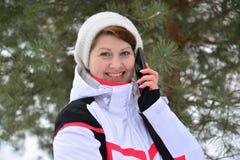 Diviértase a la mujer que habla en el teléfono en bosque del invierno del pino Imagen de archivo libre de regalías
