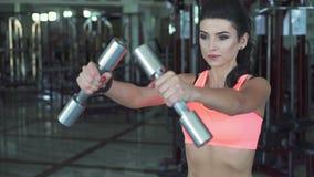 Diviértase a la mujer que hace ejercicio con pesas de gimnasia en el gimnasio lentamente metrajes