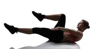 Diviértase a la mujer que hace el ejercicio del ABS y de piernas, tiro del estudio de la silueta fotografía de archivo