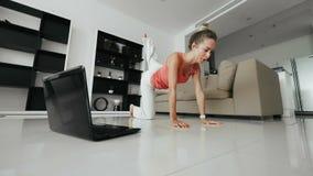 Diviértase a la mujer que hace estirando ejercicio y mirando el cuaderno en el entrenamiento casero almacen de video