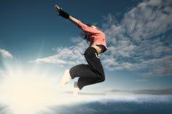 Diviértase a la mujer que salta y vuele sobre el cielo y el sol Fotografía de archivo