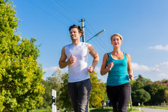 Diviértase los pares que corren y que activan en la calle rural Fotografía de archivo libre de regalías
