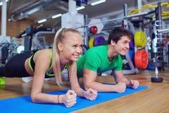 Diviértase los pares que hacen la barra de las flexiones de brazos en piso en el gimnasio Imagen de archivo