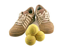 Diviértase los zapatos al lado de 4 pelotas de tenis Foto de archivo