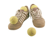 Diviértase los zapatos al lado de 4 pelotas de tenis Imagen de archivo