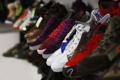 Diviértase los zapatos en colores múltiples en un estante del departamento Fotografía de archivo libre de regalías