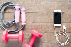 Diviértase y adiete el concepto con pesas de gimnasia y salte el traje y el smartphone en la madera Foto de archivo