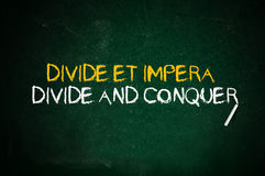 Divide and conquer. Latin quote handwritten with chalk on a green school board Royalty Free Stock Images