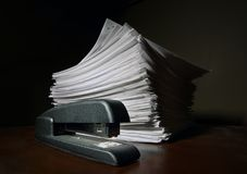 Divide and Conquer. A stapler sitting in front of a stack of stapled paper Stock Photography