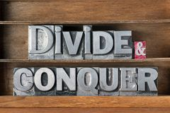 Divide and conquer tray. Divide and conquer phrase made from metallic letterpress type on wooden tray Royalty Free Stock Photography