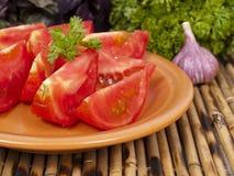 Divide un tomate en segmentos en una placa Fotos de archivo libres de regalías