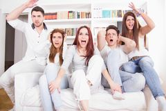 Divided friends watching game cheering for different teams Royalty Free Stock Photos