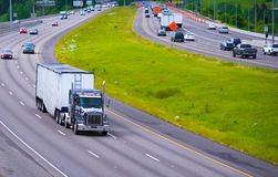 Divided Highway Curve large semi truck with bulk trailer. A broad highway with a dividing strip of grass opposite sides with a classic semi truck traffic and royalty free stock photography