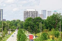 Divided highway with lots of lush foliage and green stoplight with cars and trucks and pedestrians leading to downtown Tulsa. Oklahoma USA stock photography