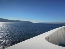 Divided screen of blue sky, far islands, deep blue ocean and white ship in Aegean Sea, Greece stock photography